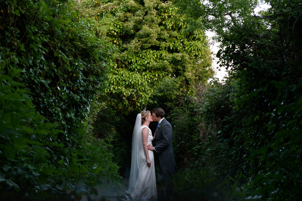 bride and groom kissing in tree tunnel to the coast