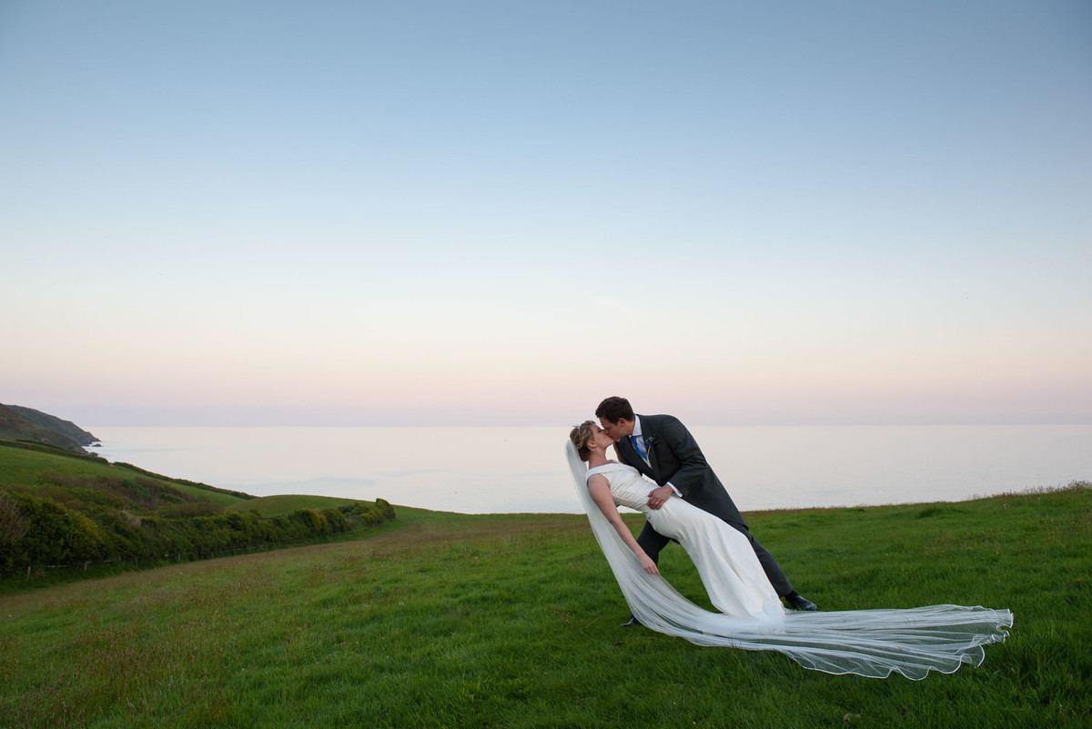 dramatic kiss between bride and groom on the Cornish coast with the sea behind