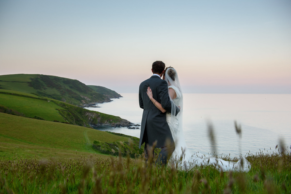 bride and groom in embrace looking at the coastline views